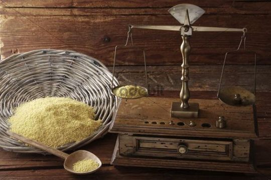 Antique scales weighing grains of Millet (Panicum miliaceum) on a wooden surface