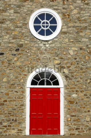 Red door and white round window of the Saint-Pierre-et-Saint-Paul Church, historic monument in the town of St-Pierre-de-l´Ile-d´Orleans, on Orléans Island, Quebec, Canada