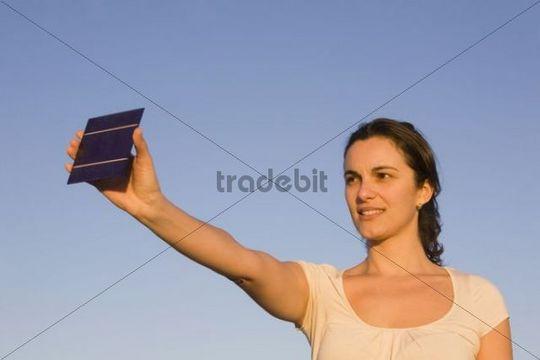 Woman holding a solar panel towards the sun