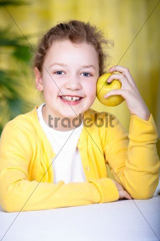 8-year-old girl at a table with an apple