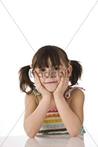Girl with pigtails sitting at a table leaning on her hands