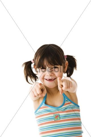 Smiling little girl with pigtails pointing forward