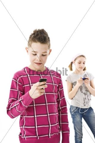 Boy with a mobile phone and a girl with an iPod