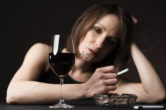 Smoking woman with a glass of wine