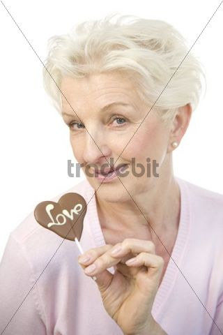 """A mature woman holding a chocolate heart with the word """"Love"""" in her hand"""
