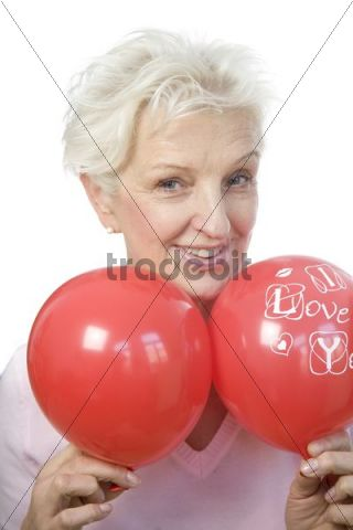 "A mature woman holding two red balloons, saying ""I love you"""