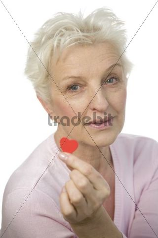 A mature woman holding a red heart between her fingers