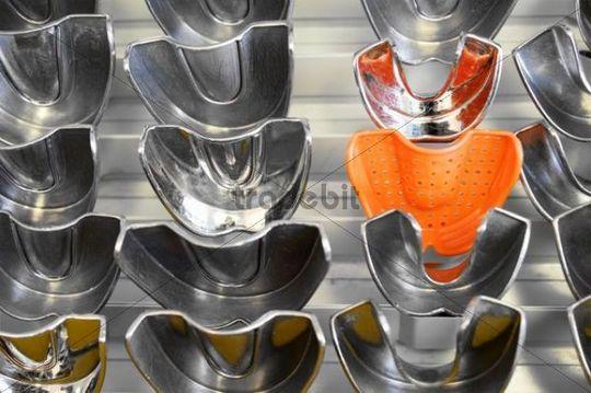 Plastic form amidst metal forms for dental imprints, Germany, Europe