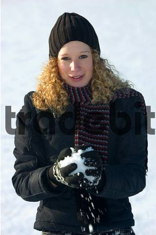a young woman forming a snowball