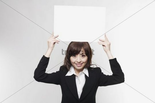 Young Asian business woman holding a blank piece of paper above her head