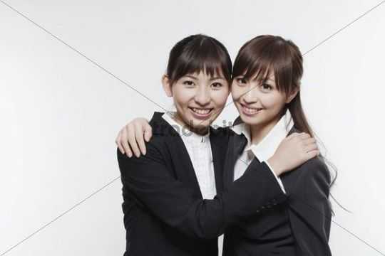 Two young Asian business women, hugging