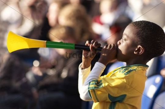 Small South African boy as a fan of the national football team of South Africa for the 2010 World Cup with Vuvuzela and flag