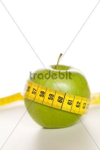 Green apple with a yellow tape measure