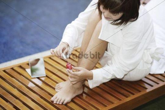 Young Asian woman applying nail polish