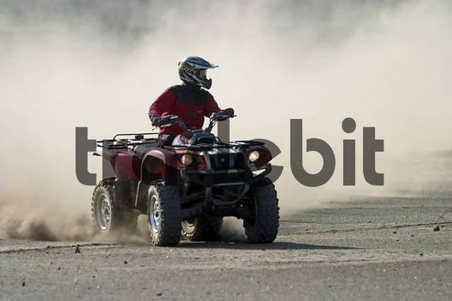 Quad drives on dusty piste