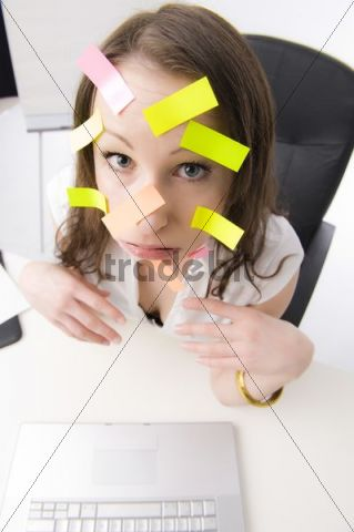 Office worker with many post-its on her face