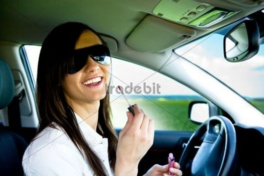 Young woman putting on makeup in the car