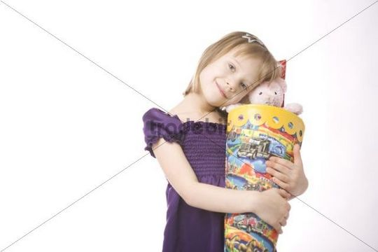 Girl hugging a large cornet of cardboard filled with sweets and little presents given to children in Germany on their first day at school