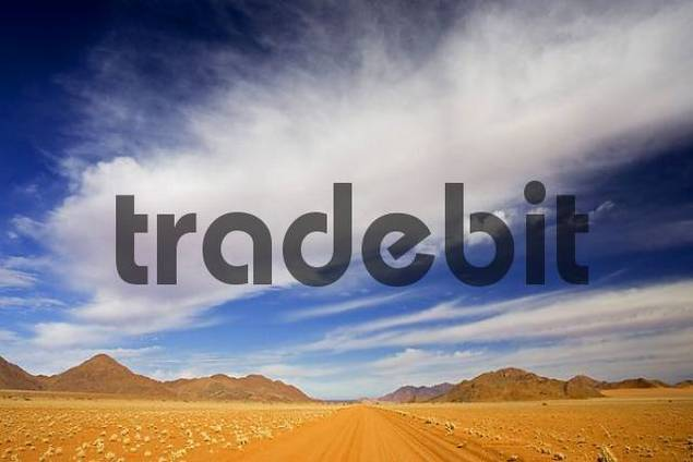 Red sandy road through the desert with mountains and clouds. Tiras Mountains and Namib Desert, Namibia