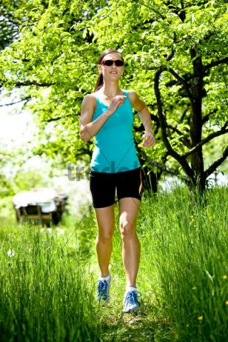 Young woman jogging through an orchard