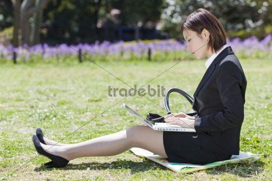 Businesswoman sitting on lawn, using laptop