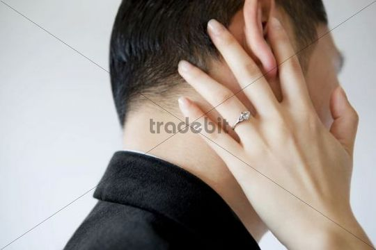 Woman´s hand with a wedding ring caressing man´s face