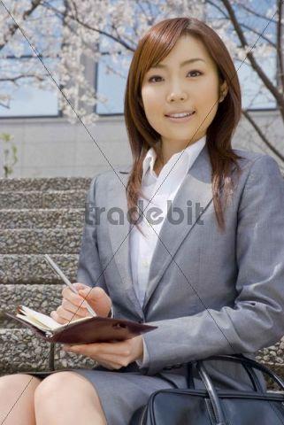 Businesswoman sitting under cherry blossom tree