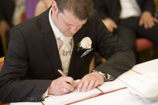 Groom signing marriage certificate at the registry office