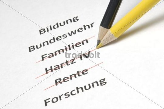 """A yellow and a black pencil crossing out the letterings """"Familien"""", """"Hartz IV"""" and """"Rente"""", German for """"families"""", """"Hartz IV"""", a German unemployme"""