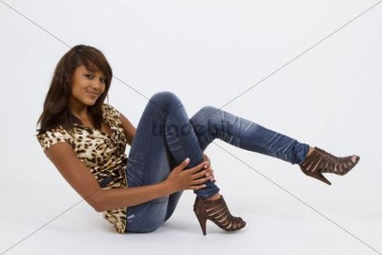 Young woman wearing a leopard-print top, jeans leggings and high heels, posing on floor