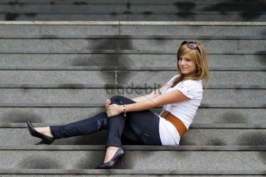 Young woman posing on stone stairs