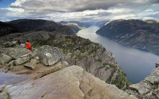Hikers at Preikestolen, Prekestolen, Preacher´s Pulpit or Pulpit Rock, above Lysefjord, Forsand, Rogaland, Norway, Scandinavia, Europe