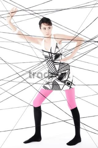 Woman, 24, dressed in the style of the 60s, standing between spanned threads, symbolic image network