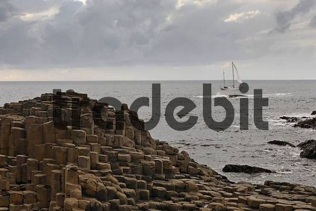 sailing ship and basalt columns of the Giants Causeway, Londonderry, North Ireland