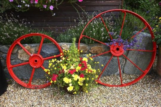Flower Decoration And Old Wagon Wheels At A House In St. Peter Port,  Guernsey