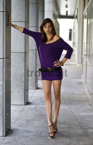 Young woman wearing a short purple dress and high heels, leaning against a column