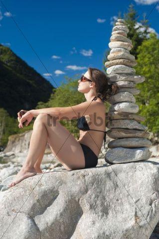 Woman in bikini next to a stone pyramid, Valle Verzasca, Tessin, Switzerland, Europe