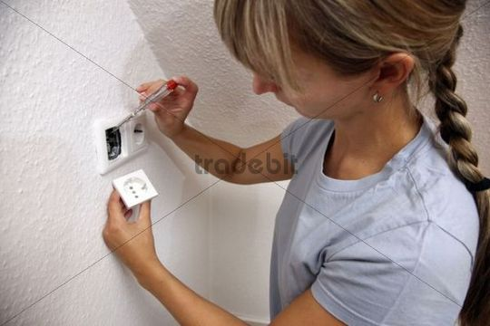 Young woman installing a power socket