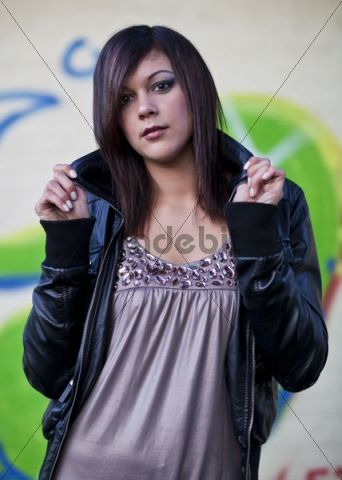 Young dark-haired woman wearing a pink dress and a dark leather jacket posing in front of a wall with graffiti
