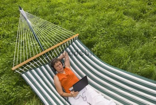 Senior woman with netbook and headset lying in a hammock