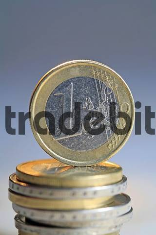 One Euro coin is standing up to a pile of Euro coins