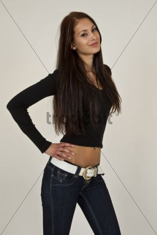 Young Woman With Long Brown Hair Black Top And Blue Jeans