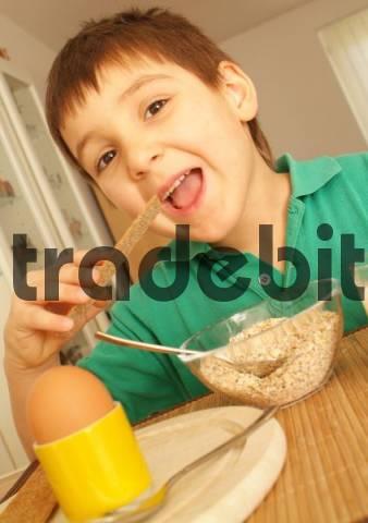 boy eats healthy breakfast with egg, oat flakes and crispbread