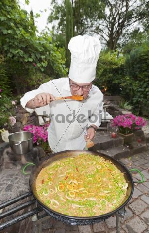 Cook preparing a paella, a Spanish rice dish, adding saffron, tasting, series, no. 1