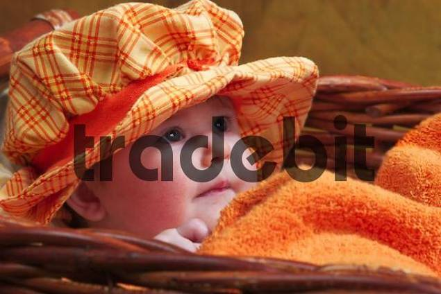 Five month old baby with a sweet hat in a wicker basket