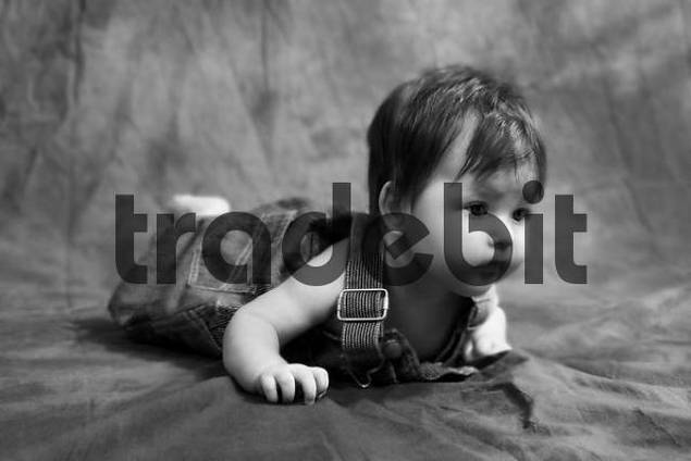 Five month old girl crawling on the floor wearing a jeans overall