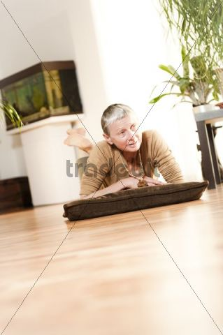 Woman, 60+, lying, relaxing on the floor in the living room