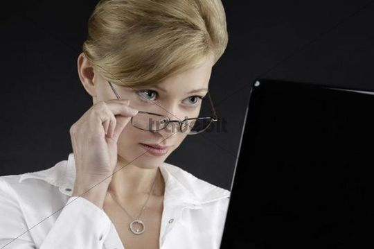 Young businesswoman with a surprized expression looking at a computer display over eyeglasses