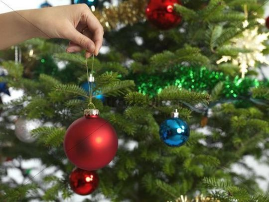 hand holding christmas bauble decorating a christmas tree - People Decorating A Christmas Tree