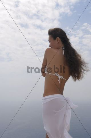 Young woman standing at a sea shore with her hair flying in the wind